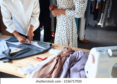 Work, create new dress. Clothes designer and potential client in workplace discuss suitable sizes for clothing