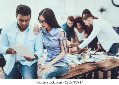 Work. Design. Brainstorm. Asian Girl. Man of Indian. Examine Documents. Man and Woman. Project. Teamwork. Working Desks. Large Bright Office. Cooperation. Different Nationalities. Table. Company.