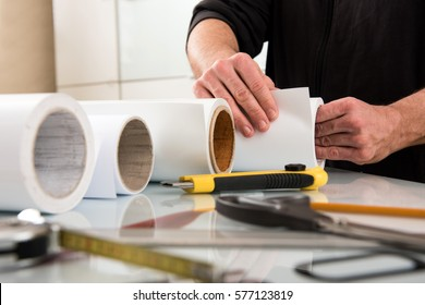 Work of designer in printing house, incognito male hands choosing paper roll for wide format printer, with tools on table in foreground