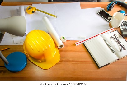 Work desk and architect's work equipment in the office, Yellow safety hard hat.