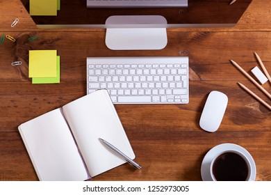 Work desk with computer monitor keyboard open notebook and coffee, modern desktop pc and supplies on workplace brown wooden business office table, device for education background, top view from above