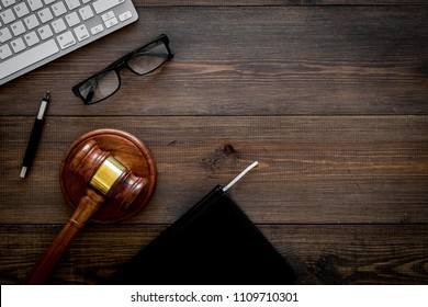 Work desk of contemporary lawyer. Lawyer office concept. Judge gavel near computer keyboard, respectable notebook on dark wooden background top view copy space