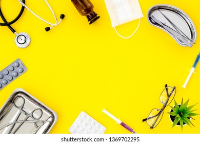 work desk of doctor in hospital with medical set frame on yellow background top view mockup
