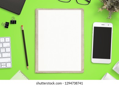 Work desk with empty paper on folder for sketch mockup. Smart phone mockup beside. Top view, flat lay.