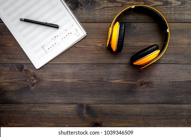 Work desk of modern composer. Music notes near headphones on dark wooden background top view copy space