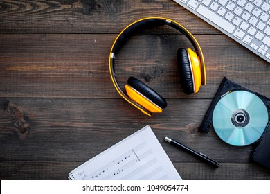 Work desk of modern composer. Music notes near headphones on wooden background top view copy space