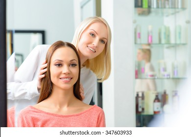 Work is done. Appealing professional is showing the front of brand new hairdo to her client.