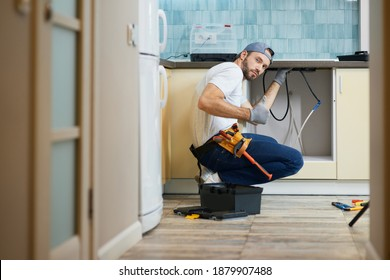 The work is done. Young repairman, professional plumber wearing tool belt looking at camera and showing thumbs up while crouching on the floor, fixing a pipe in the kitchen indoors