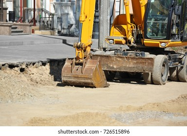 Work of excavating machine on road construction site