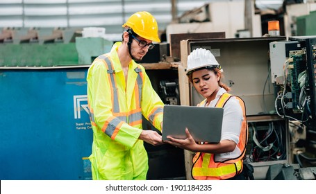 Work at factory.engineer and worker team working together in safety jumpsuit uniform with white and yellow helmet using laptop computer.in factory workshop industry concept professional