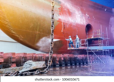Work in floating dry dock with water jet cleans the shipboard and have movement of people of the ship from sea vegetation before sandblast and paint