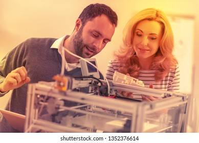 Work of the future. Man and woman tinkering with the 3D printer in their office.