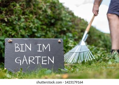"""Work in the garden. Man is raking leaves of a freshly cut hornbeam hedge. The German sentence """"Bin im Garten"""" (""""I'm in the garden"""" in English) is written on a slate."""