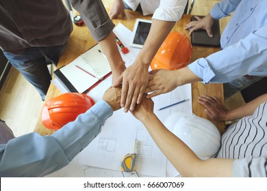 Work Group of Gngineer  people joining hands.(tool ,paper and Safety Helmet)