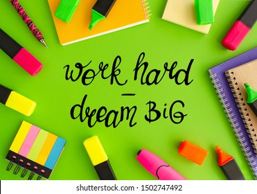 Work hard dream big. Different stationery on the green background with handwritten lettering, top view. Business and education theme. Work place, flat lay. Marketing, management, development
