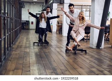 Work hard play hard. Four young cheerful business people in formal wear having fun while racing on office chairs and smiling - Shutterstock ID 1922259518