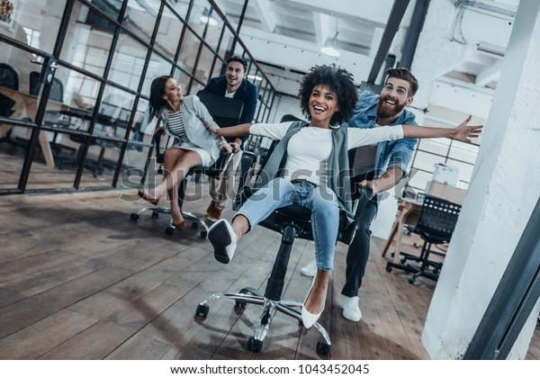 Travaille dur à jouer !  Quatre jeunes hommes d'affaires joyeux vêtus d'un vêtement élégant et décontracté s'amusant en courant sur des fauteuils de bureau et souriant