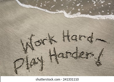 Work hard, play harder, a message written in the sand at the beach.