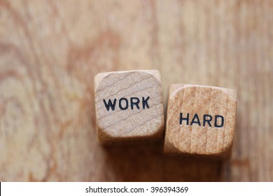 """""""Work hard"""" printed on two wood dice against wood background open for copy"""