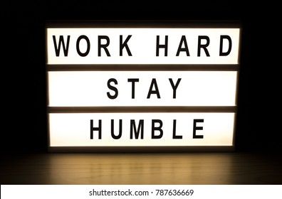 Work hard stay humble light box sign board on wooden table.