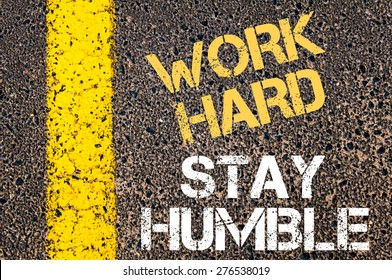 WORK HARD STAY HUMBLE  motivational quote. Yellow paint line on the road against asphalt background. Concept image