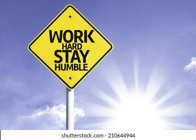 Work Hard, Stay Humble road sign with sun background