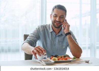 Work Hard. Think Hard. Eat Right. Smiling handsome businessman eating sushi