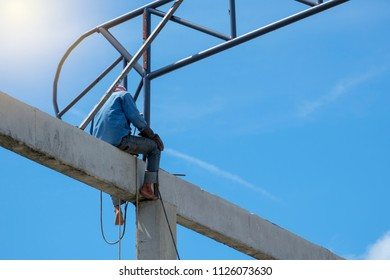 work at height, Worker sitting on concrete beam and welding structure of factory roof in construction site, High risk occupation.