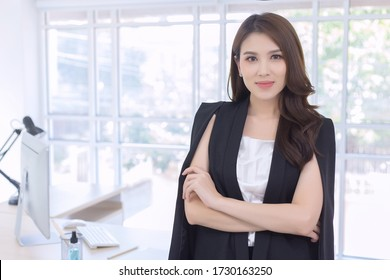 Work from home. Beautiful office lady standing and smiling at work happily.