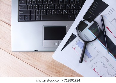 Work at home a computer with a magnifying glass on a wooden table and Analyzing the stock market