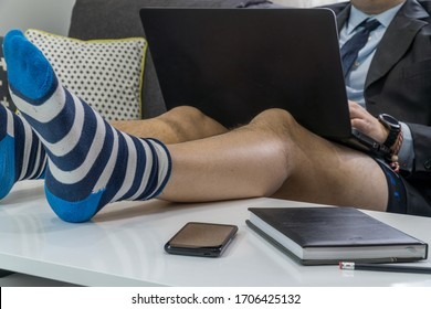 Work from home concept. Businessman having a conference call on a laptop with no pants and his legs on the table