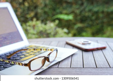 Work from home concept, glasses with laptop and copy space with garden background