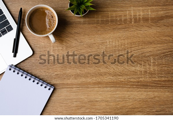 Work from home. desk office with laptop, blank notepad, coffee cup and pen on wood table. Flat lay top view copy spce.