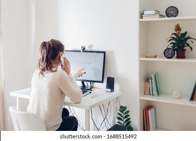Work from home during coromavirus pandemic. Woman stays home talking on phone. Workspace of freelancer. Office interior with computer