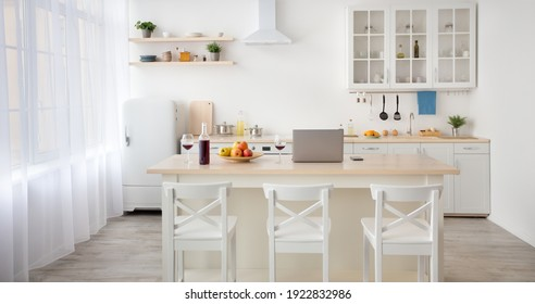 Work from home, freelance, interior blog and simple design. Laptop, fruits and wine on table, white furniture with utensils, shelves with dishes and plants in pot, refrigerator in the dining room