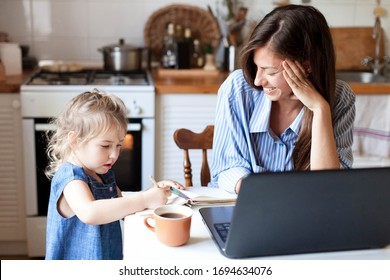 Work from home office with kid. Working mother using laptop. Cozy freelance workplace at kitchen table. Happy female business, woman career. Cute child drawing in mom notebook. Lifestyle family moment