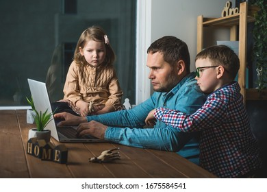 Work from home on laptop. Father and children boy and girl sitting on the table.