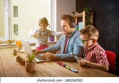 Arbeite von zu Hause aus. Schulunterricht während der Quarantäne. Vater arbeitet mit Kindern Junge und Mädchen auf dem Tisch.