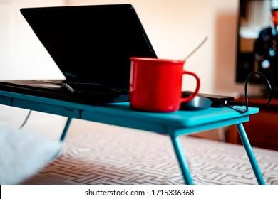 Work from home workspace set-up during Coronavirus pandemic. Red mug, laptop,portable hard disk and lap desk.