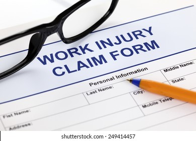 Work Injury claim form glasses and ballpoint pen