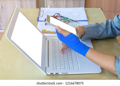 work injury. injured woman hand sore with blue elastic bandage on hand, wrist pain from using computer, office syndrome.