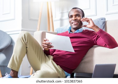 Work issues. Positive nice self employed man holding a document and making a cal while being engaged with work