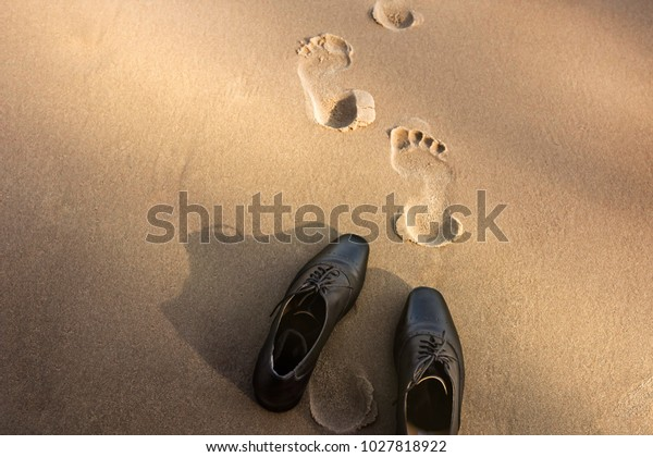 Work Life Balance Concept, Businessman take off his Working Oxford Shoes and leave it on the Sand Beach for Walk into the Sea on Sunny Day. Top View