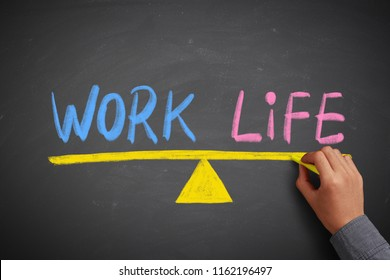 Work and life balance concept on the chalkboard with writing hand.