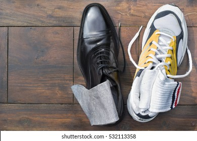 Work life balance. An elegant business shoe (oxford style) and a running shoe. Each with socks. Use as symbol for the concept 'work life balance'. Copy space to the left.