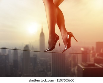 Work life balance employment concept: Business woman balancing on the rope high above the city
