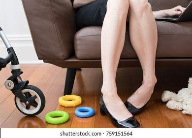 Work life balance, working mother juggling life, job and children. Woman is wear pump heels and is seated on a lounge next to her pram and surrounded by toys