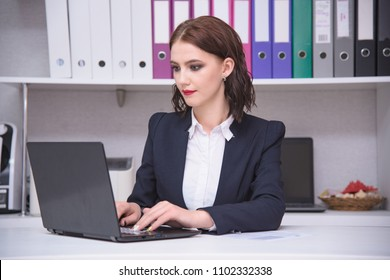 I work in the office. Portrait of a beautiful brunette manager girl in an office working behind a laptop. She sits right in front of the camera smiling and looks serious
