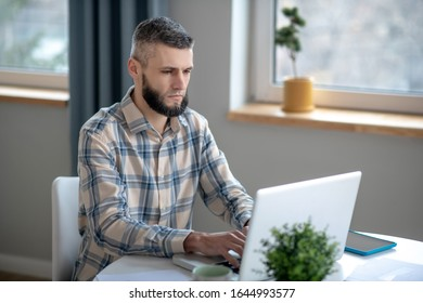Work on netbook. Young smart attentive man sitting at a table and working at a white netbook.