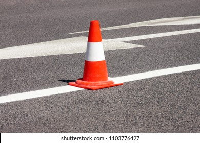 Work on road. Construction cone. Traffic cone, with white and orange stripes on asphalt. Street and traffic signs for signaling. Road maintenance, under construction sign and traffic cone on road.